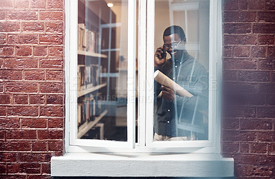 Buy stock photo Cropped shot of a handsome young male architect taking a phonecall while standing at his office window