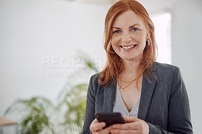 Buy stock photo Portrait of a mature businesswoman using a cellphone in an office