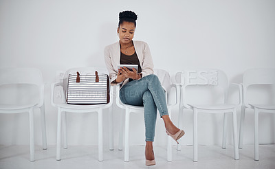 Buy stock photo Shot of a young businesswoman using a digital tablet while sitting in a line against a white background