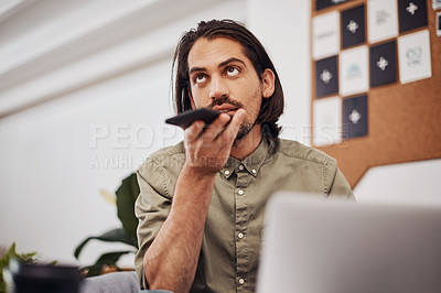 Buy stock photo Shot of a young businessman talking on a cellphone while using a laptop in an office