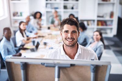 Buy stock photo Portrait of a young businessman using a whiteboard while giving a presentation to his colleagues in an office
