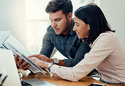 Buy stock photo Cropped shot of two young businesspeople sitting together in the office and going through paperwork