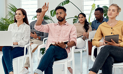 Buy stock photo Cropped shot of a handsome young businessman sitting with his colleagues and raising his hand during an office presentation