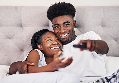 Buy stock photo Shot of a young man using a remote control while lying in bed with his girlfriend