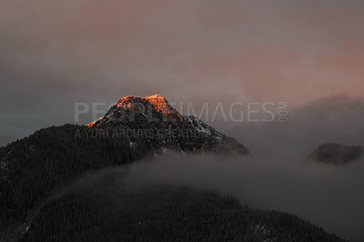 Buy stock photo Shot of clouds covering beautiful mountain and forest scenery at sunset in the East Kootenay region of British Columbia, Canada