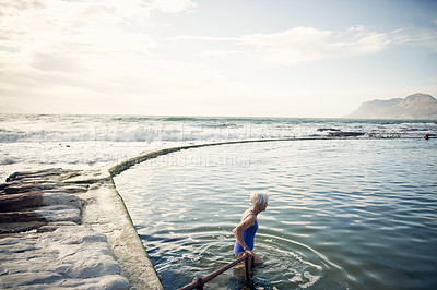 Buy stock photo Cropped shot of a senior woman swimming outdoors in the ocean