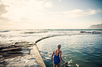 Buy stock photo Rearview shot of a senior woman swimming outdoors in the ocean