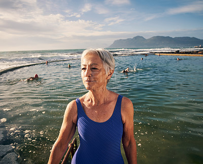 Buy stock photo Shot of an attractive senior woman swimming outdoors in the ocean