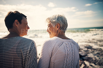 Buy stock photo Rearview shot of a senior woman bonding and spending time with her adult daughter at the beach