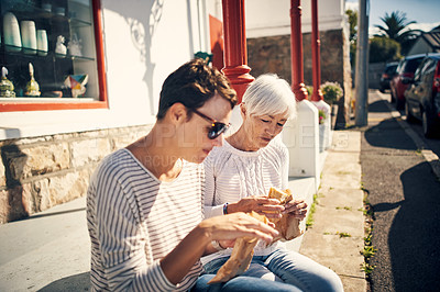 Buy stock photo Cropped shot of a senior woman having lunch and bonding with her adult daughter outdoors in the city