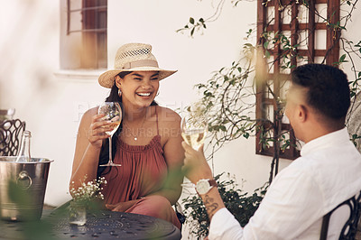 Buy stock photo Cropped shot of a happy young couple enjoying a glass of wine while sitting outside