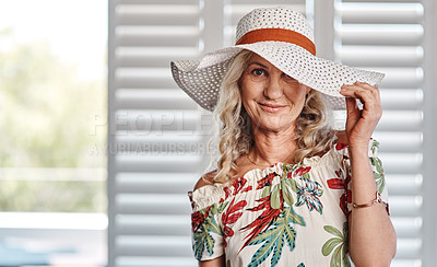 Buy stock photo Cropped portrait of an attractive senior woman wearing a summer hat while standing indoors during the day