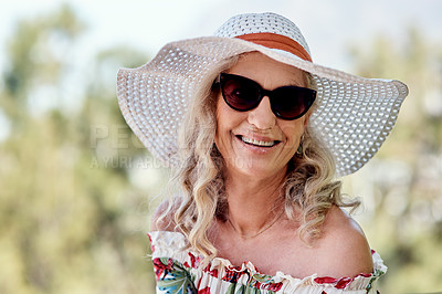 Buy stock photo Cropped portrait of an attractive senior woman smiling while sitting outdoors on a summer's day