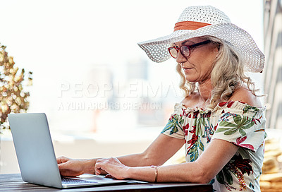 Buy stock photo Cropped shot of an attractive senior woman using a laptop while sitting outside at home
