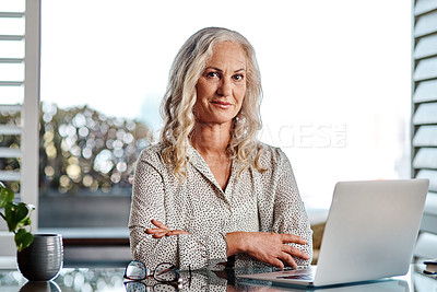 Buy stock photo Cropped portrait of an attractive senior businesswoman using a laptop while working from home