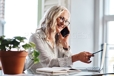 Buy stock photo Cropped shot of an attractive senior businesswoman taking a phonecall while working from home