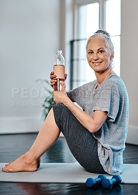 Buy stock photo Portrait of a cheerful mature woman practicing yoga while having a drink of water inside of a studio during the day