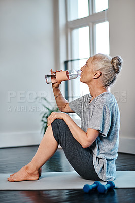 Buy stock photo Shot of a mature woman practicing yoga while having a drink of water inside of a studio during the day