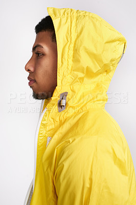 Buy stock photo Studio shot of a handsome young man wearing a bright yellow hoodie while standing against a grey background inside of a studio