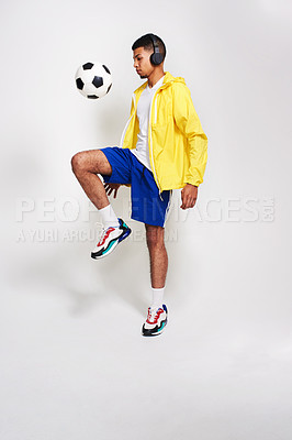 Buy stock photo Studio shot of a handsome young man listening to music while kicking a soccer ball in the air inside of a studio