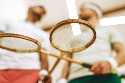 Buy stock photo Cropped shot of two young men crossing their racquets at a squash court