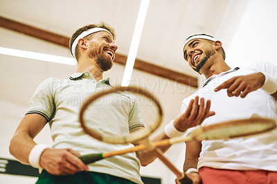 Buy stock photo Shot of two young men crossing their racquets at a squash court