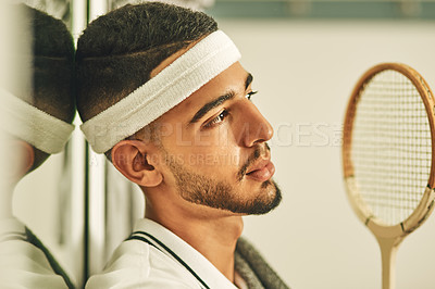 Buy stock photo Shot of a young man looking thoughtful in the locker room after a game of squash