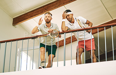 Buy stock photo Shot of two young men watching a game of squash from the viewing gallery