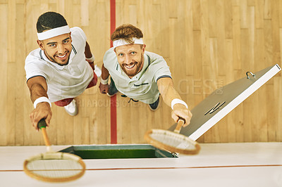 Buy stock photo High angle shot of two young men holding up their rackets at a squash court