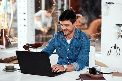 Buy stock photo Cropped shot of a handsome young businessman working on a laptop in an office inside his workshop