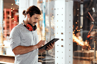 Buy stock photo Cropped shot of a handsome young businessman using a digital tablet in an office inside his workshop