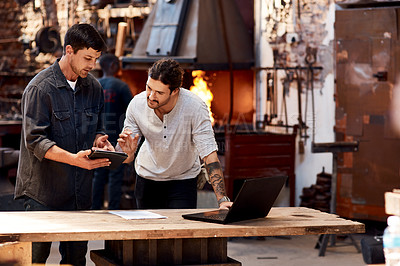 Buy stock photo Cropped shot of two handsome young using their digital devices while working together inside their workshop
