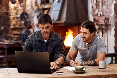 Buy stock photo Cropped shot of two handsome young using a laptop while working together inside their workshop
