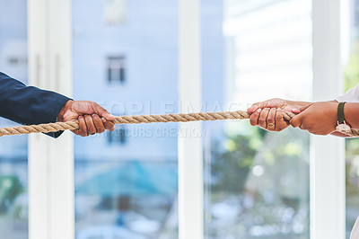 Buy stock photo Shot of two unrecognisable businesspeople pulling on a rope during tug of war in an office