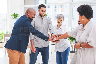Buy stock photo Shot of a group of businesspeople joining their hands together in a huddle