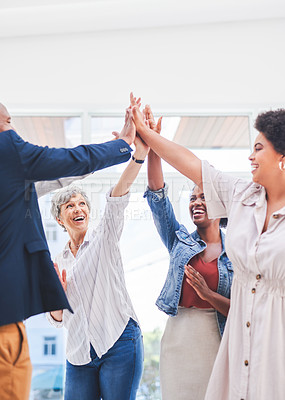 Buy stock photo Shot of a group of businesspeople giving each other a high five in an office