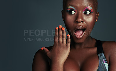 Buy stock photo Shot of a beautiful young woman looking surprised while posing against a grey background