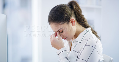 Buy stock photo Shot of a young businesswoman looking stressed out while working on a computer in an office