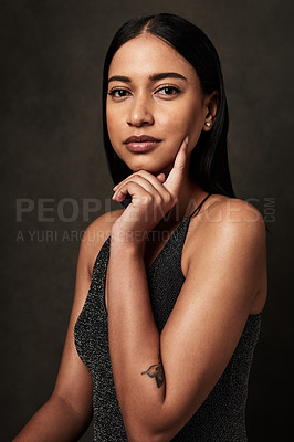 Buy stock photo Cropped portrait of an attractive young woman wearing a formal dress and sitting against a dark background in the studio