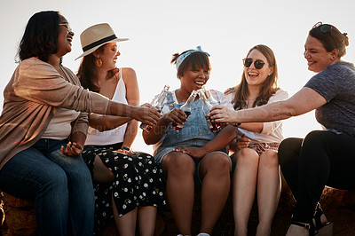 Buy stock photo Cropped shot of a group of young girlfriends making a toast with beer bottles while sitting at the beach