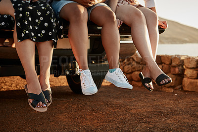 Buy stock photo Cropped shot of a group of unrecognizable girlfriends sitting on top of a car outdoors during the day