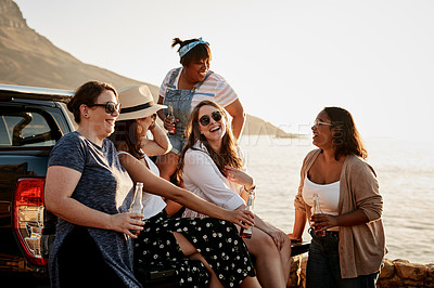 Buy stock photo Cropped shot of a group of young friends having beer and laughing together while hanging out at the beach