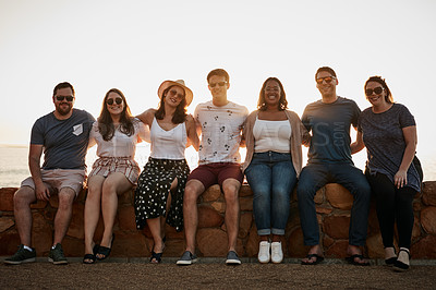 Buy stock photo Full length portrait of a group of young friends embracing each other while sitting together at the beach