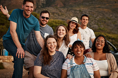 Buy stock photo Cropped portrait of a group of young friends smiling while hanging out together at the beach during the day