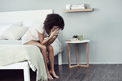 Buy stock photo Shot of a young woman suffering from depression in her bedroom