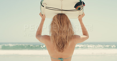 Buy stock photo Cropped shot of an attractive young woman carrying her surfboard at the beach