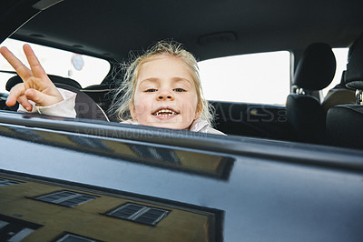Buy stock photo Portrait of an adorable little girl hanging out the window of a car