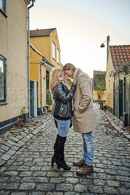 Buy stock photo Full length shot of an affectionate young couple embracing outdoors while traveling together in a foreign town