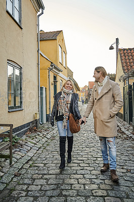 Buy stock photo Full length shot of a happy young couple traveling and walking together outdoors in a foreign town