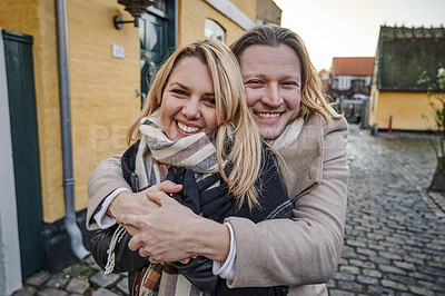 Buy stock photo Portrait of a happy young couple embracing outdoors while traveling together in a foreign town